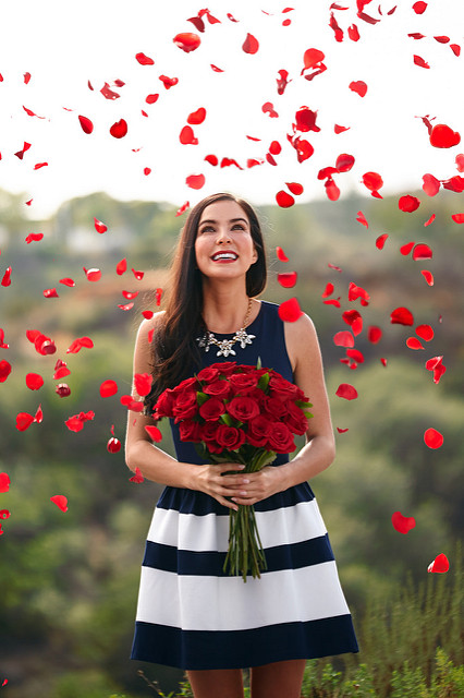 woman happy red roses petals rain love valentine's day
